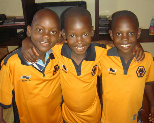 three young children smiling while wearing recycled clothing